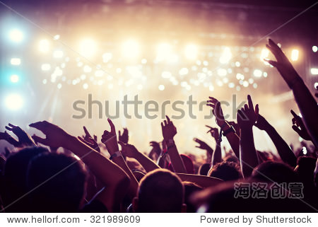 Audience with hands raised at a music festival and lights streaming down from above the stage. Soft focus  high ISO  grainy image.