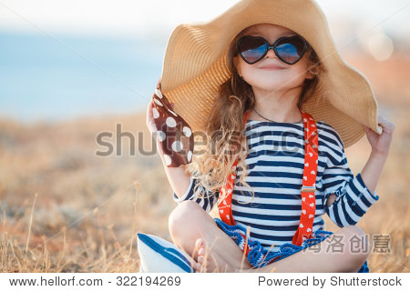 Pretty little girl in a striped dress and hat relaxing on the beach near sea  summer  vacation  travel concept. smiling cute little girl on beach vacation. Baby girl in hat and sun glasses on beach