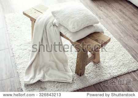Still life details  stack of white cushions and blanket on rustic bench on white carpet
