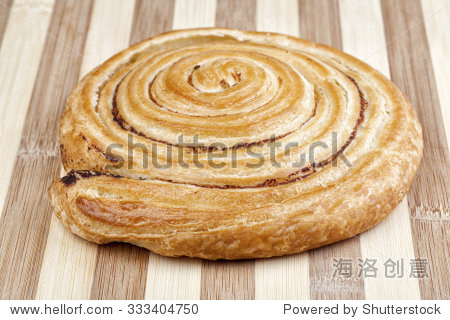 Closeup shot of danish pastry swirl with milled hops. Studio shot on wooden table.