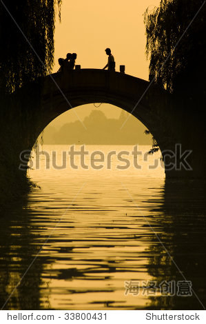 silhouette of people walking on a bridge in xihu,haongzhou, china