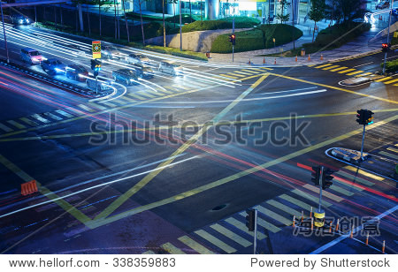 A high angle view of  treet intersection  with yellow cross walk markings  traffic signal lights  and curb cuts.