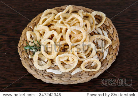 Fried onion rings with rosemary branch on the wood background