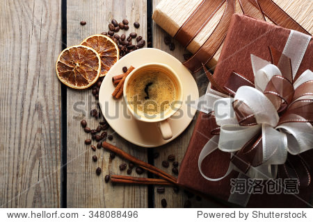Beautiful gift  cup with coffee and coffee grains on wooden background