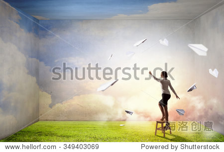 Businesswoman standing on chair and reaching hand to touch something
