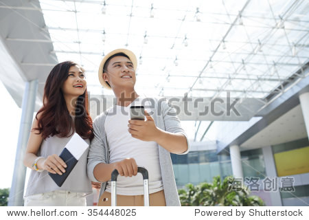 Young Vietnamese couple in the airport waiting for departure