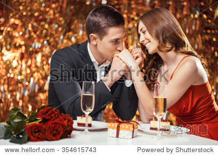 Romantic photo of beautiful couple on glitter gold background. Couple having date at Valentine's Day. Lovers having dinner. There are glasses with champagne  desserts  roses and gift on table
