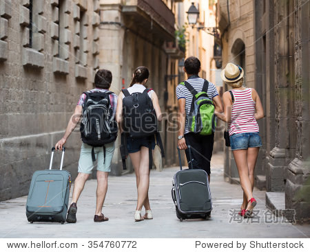 Group of young friends walking through the city with travel bags. Back view