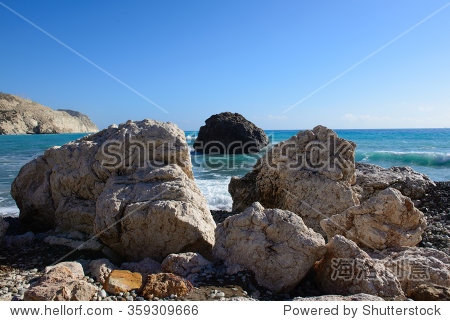 Big sharp rocks on the beach and the black stone in the sea