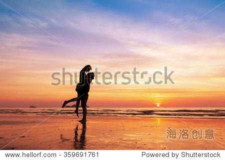 Couple kissing on the beach with a beautiful sunset in background  man lifting the woman