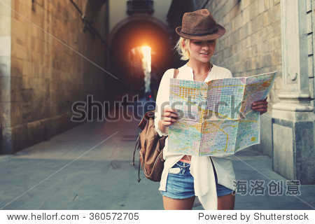 Cheerful woman wanderer with trendy look searching direction on location map while traveling abroad in summer  happy female tourist searching road to hotel on atlas in a foreign city during vacation