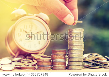 Close up of male hand stacking gold coins with green bokeh background  Business Finance and Money concept Save money for prepare in the future.