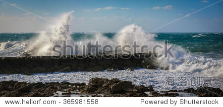 Big waves breaking on the shore with sea foam and blue cloudy sky