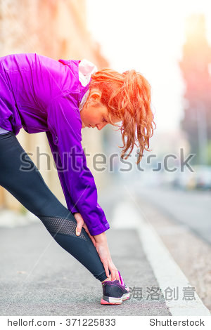 Girl doing stretching on the sidewalk in the city