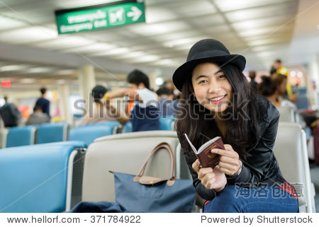 Beautiful Asian woman solo traveler holding passport and waiting for flight travel at airport terminal