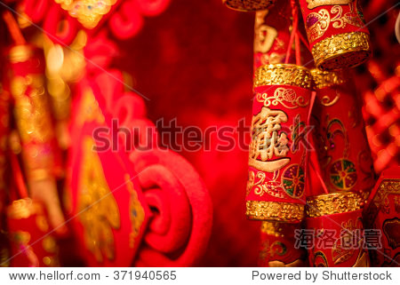 Traditional Chinese new year decorations. Chinese red firecrackers with the symbol of money. Red background.