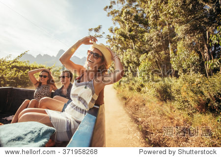 Portrait of a cheerful young woman sitting in the back of pickup truck with friends. Young people enjoying on a road trip.