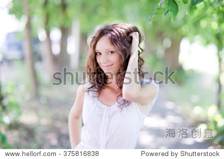 Summer portrait of young attractive girl posing in the park