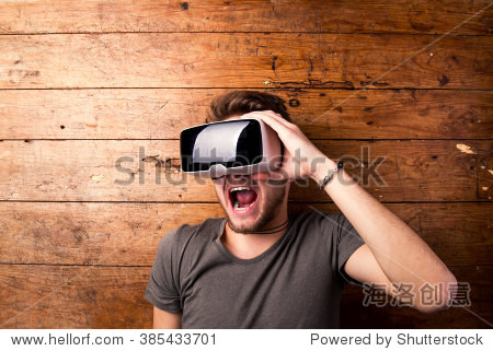 Man wearing virtual reality goggles. Studio shot, wooden background