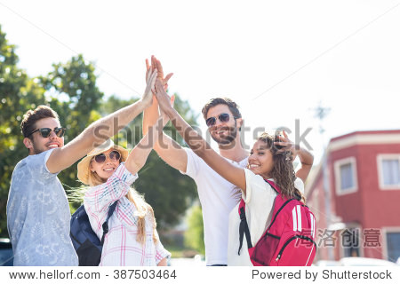 Hip friends doing high-five in the city