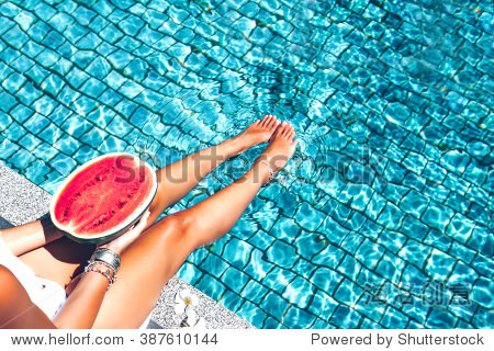 Girl holding watermelon in the blue pool  slim legs  instagram style. Tropical fruit diet. Summer holiday idyllic.