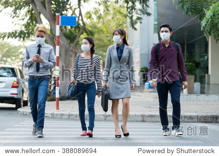 Asian people in moth masks crossing road in the city
