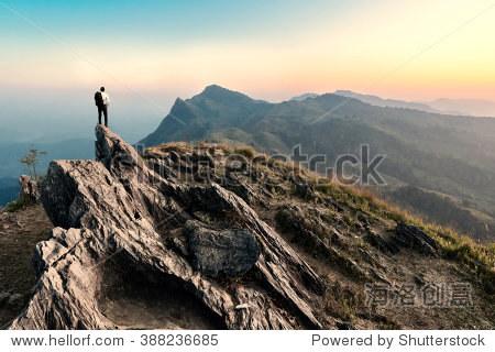 businessman hike on the peak of rocks mountain at sunset  success winner  leader concept
