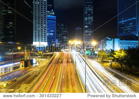 traffic on city road through modern buildings in hong kong