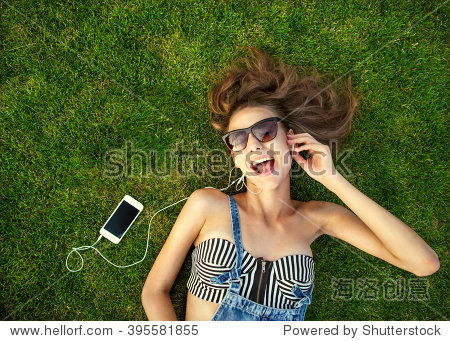girl lying on the green grass  listening to music