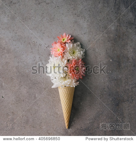 Pink and white flowers in ice cream cone on marble background. Minimal concept. Flat lay.