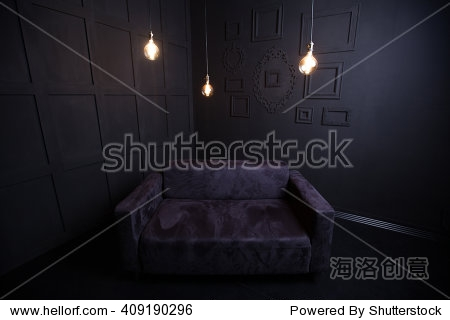 Black Sofa in a dark room with light bulb