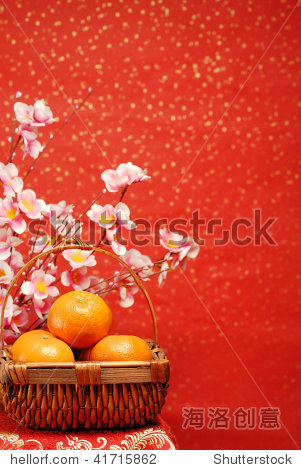 Chinese new year decoration--A basket of oranges with plum flower on a festive background.
