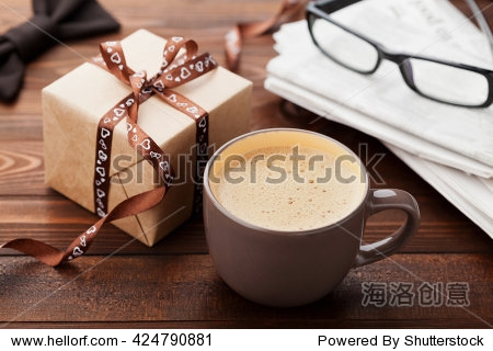 Morning cup of coffee  gift  newspaper  glasses and bowtie on wooden desk for breakfast on Happy Fathers Day