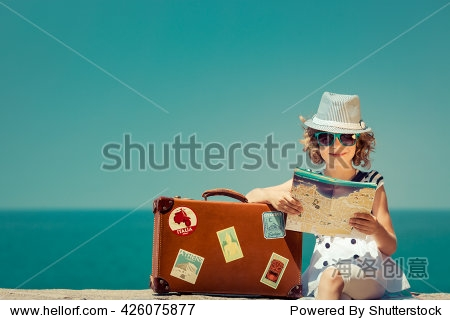 Child with vintage suitcase and city map on summer vacation. Travel and adventure concept