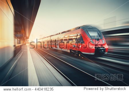 Beautiful railway station with modern high speed red commuter train with motion blur effect at colorful sunset in Nuremberg  Germany. Railroad with vintage toning