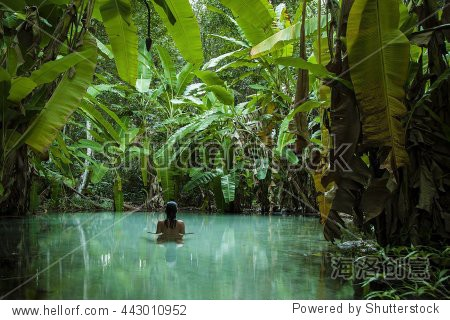 A girl swims in a natural pool surrounded by banana trees