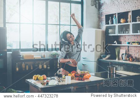 Cooking with passion. Beautiful young mixed race woman in headphones cooking salad and dancing while standing in kitchen at home