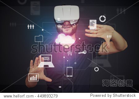 Young bearded man in VR-headset is surrounded by virtual data on interactive touch screen over dark background
