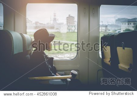 Enjoying travel. Young pretty woman traveling by the japan classic train from hakata to yufuin Japan (Limited Express Yufuin no Mori) sitting near the window. vintage filter.