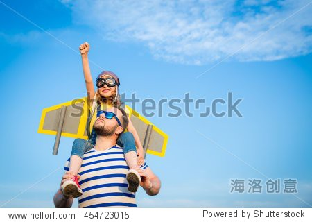 Kid with jet pack pretend to be superhero. Child playing with father in summer. Happy dad and son outdoors. Success  leader and winner concept