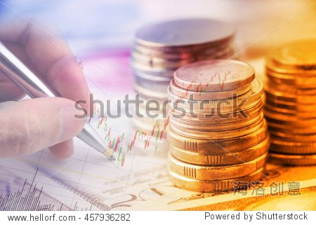 Closeup view : Stack of coins and a hand holding a ballpoint pen is examining a technical chart of financial instrument. An idea / concept of currency trading, making a decision for an optimal gain.