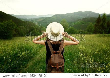 woman traveler with backpack holding hat and looking at amazing mountains and forest  wanderlust travel concept  space for text  atmospheric epic moment