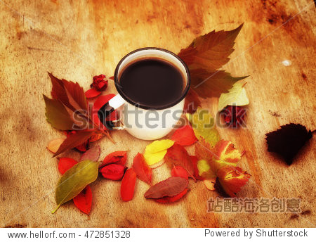 enamel coffee cup on the old wooden background in grunge style with autumn leaves rural retro style