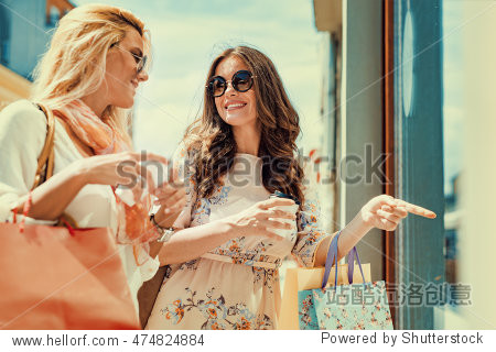 Happy woman with shopping bags pointing finger in the shop window