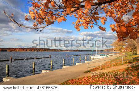 Boats docked in a lake by the autumn trees