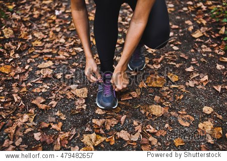 Young girl athlete tying up laces on her sport shoes before training on autumn forest path. Lots of yellow and orange leaves on a ground in park. All-weather training and season concept. Front view