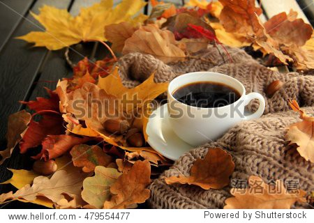 Autumn  fall leaves  hot steaming cup of coffee and a warm scarf on wooden table background. Seasonal  morning coffee  Sunday relaxing and still life concept.