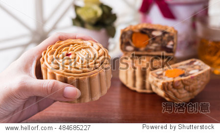 Moon cake - Mid-Autumn festival moon cake in woman hands with wooden background.