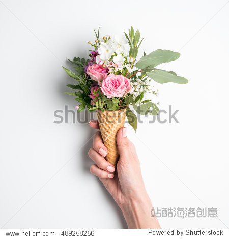 Beautiful flower in ice cream cone in girls hand with manicure on white background