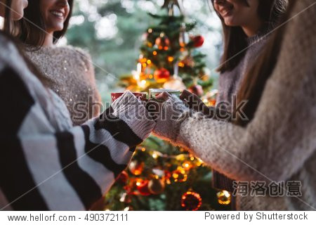 Friend celebrating together and holding cups of warm tea. Christmas tree in background. Selective focus.